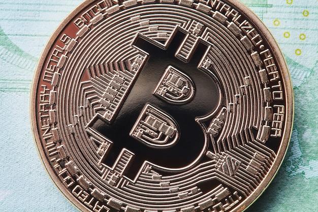 Nahaufnahme von euro-scheinen und goldmünzen-bitcoin