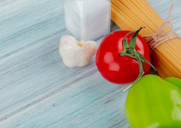 Nahaufnahme von fadennudelmakkaroni mit tomatenpfeffer knoblauch und salz auf holztisch