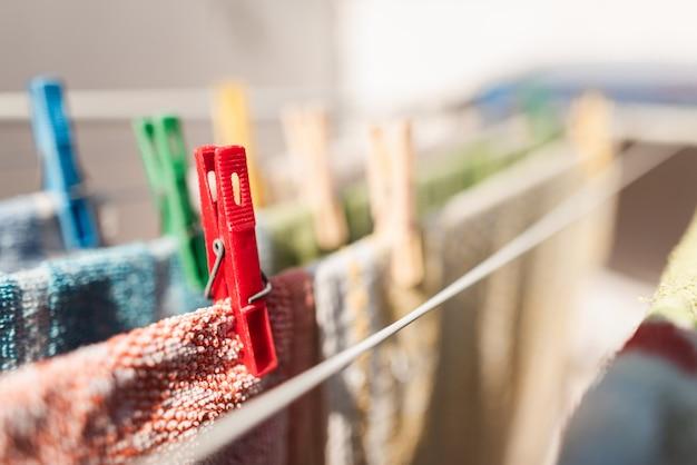 Nahaufnahme von farbigen stiften und hängenden kleidern oder küchentüchern. farbige wäscheklammern aus kunststoff auf einer wäscheleine. roter stift. hausarbeiten. hausaufgaben. wäsche. wasch die klamotten. speicherplatz kopieren.