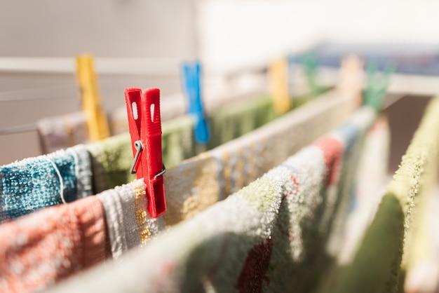 Nahaufnahme von farbigen stiften und hängenden kleidern oder küchentüchern. farbige wäscheklammern aus kunststoff auf einer wäscheleine. roter stift. hausarbeiten. hausaufgaben. wäsche. wasch die klamotten.