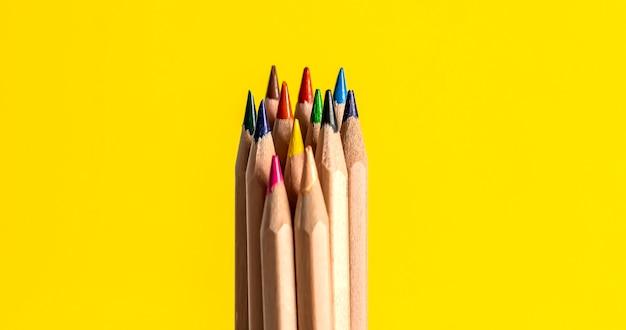 Nahaufnahme von farbstiften mit unterschiedlicher farbe über gelber oberfläche Premium Fotos