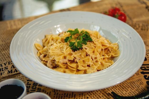 Nahaufnahme von farfalle mit champignons und hähnchen, garniert mit parmesan und petersilie