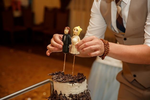 Nahaufnahme von figuren der braut und des bräutigams auf einer hochzeitstorte