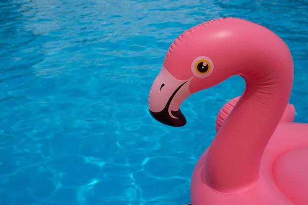 Nahaufnahme von flamingo-pool-schwimmer im blauen wasserhintergrund des swimmingpools