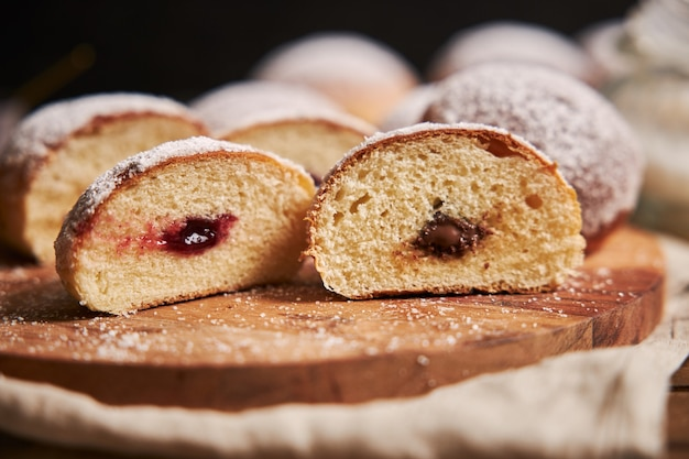 Nahaufnahme von flauschig geschnittenen donuts gefüllt mit marmelade auf einem tablett unter den lichtern