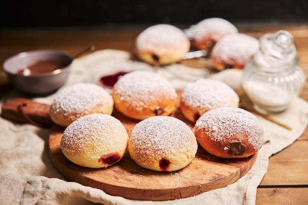 Nahaufnahme von flauschigen donuts gefüllt mit marmelade auf einem tablett auf dem tisch unter den lichtern