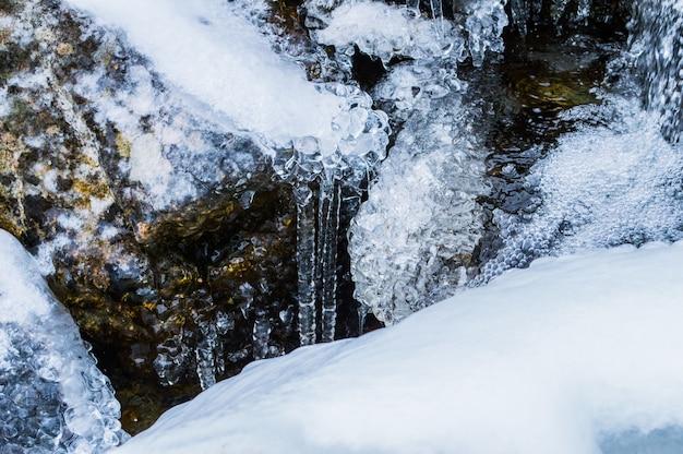 Nahaufnahme von fließendem wasser mit einem gefrorenen felsen im winter