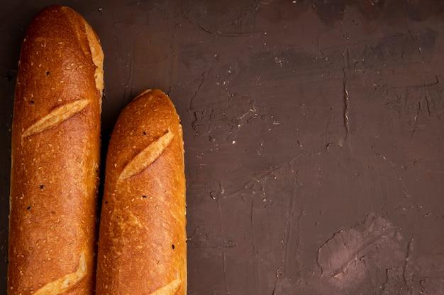 Nahaufnahme von französischen baguettes auf der linken seite und kastanienbraunem hintergrund mit kopienraum