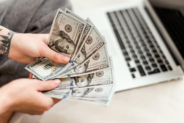Nahaufnahme von frau hände halten neue dollarnoten verdient sie online vom laptop zu hause arbeiten