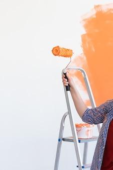 Nahaufnahme von frau malerei wand. renovierungs-, renovierungs- und reparaturkonzept.
