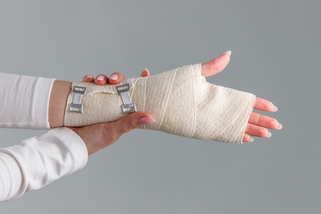 Nahaufnahme von frauenarmen, die ihr schmerzhaftes handgelenk mit flexiblem elastischem unterstützendem orthopädischem verband berühren, verursacht durch längere arbeit am laptop