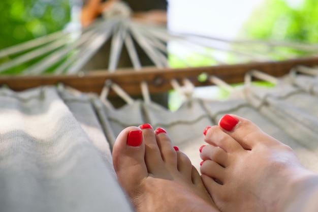 Nahaufnahme von frauenbeinen mit rotem nagellack auf hängematte. frau mit schöner pediküre, die am sonnigen sommertag auf hängematte ruht. entspannung und urlaubskonzept.