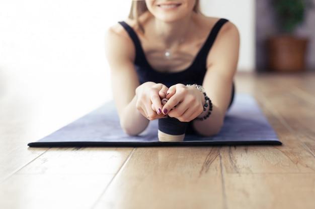 Nahaufnahme von frauenfüßen, mädchen, das yogahaltungen tut
