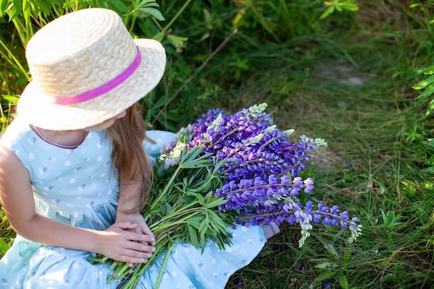 Nahaufnahme von frauenhänden, die blumenstrauß mit wildblumen halten. sommerviolette blüten. lupinenfeld. provence. kleines mädchen hält großen strauß lila lupinen im blühenden feld. naturkonzept. vorhanden