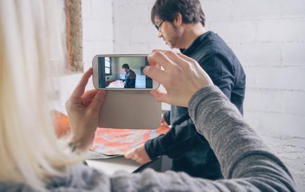 Nahaufnahme von frauenhänden, die ein foto mit einem smartphone an einen malerkünstler machen, der in einer werkstatt arbeitet