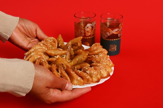 Nahaufnahme von frauenhänden, die einen teller mit köstlichen orientalischen traditionellen marokkanischen süßspeisen und minztee in einem schönen arabischen glas servieren. auf rotem hintergrund isoliert.