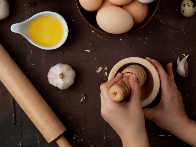 Nahaufnahme von frauenhänden, die knoblauch in knoblauchzerkleinerer mit buttereiernollnadel drücken