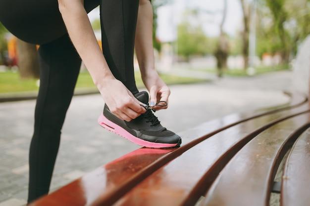 Nahaufnahme von frauenhänden, die schnürsenkel an weiblichen schwarzen und rosa turnschuhen beim training auf der bank im freien binden