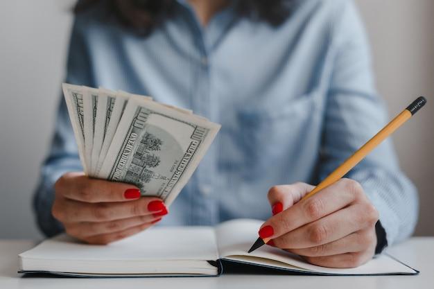 Nahaufnahme von frauenhänden mit roten nägeln, die hundert-dollar-geldbanknoten halten und notizen mit einem bleistift machen