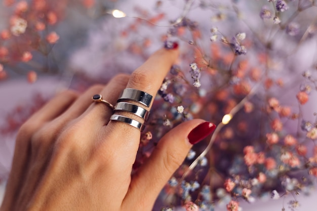 Nahaufnahme von frauenhandfingern, die zwei ringe tragen