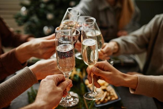Nahaufnahme von freunden, die champagnergläser anstoßen, während sie gemeinsam das weihnachtsessen genießen, das von e...