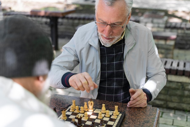 Nahaufnahme von freunden, die draußen schach spielen playing