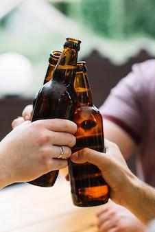 Nahaufnahme von freunden, die mit braunen flaschen klirren
