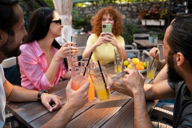 Nahaufnahme von freunden, die mit getränken am tisch sitzen