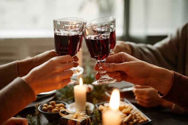 Nahaufnahme von freunden, die zusammen weihnachtsessen genießen und im sitzen mit weingläsern anstoßen ...