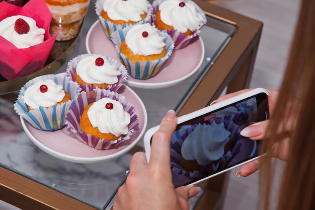 Nahaufnahme von frisch gebackenen kuchen und cupcakes in folge am tisch. gesundes sommergebäckdessert. beerentörtchen oder kuchen mit frischkäse-draufsicht. copyright-bereich für website