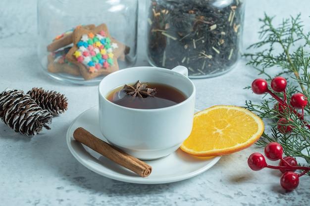 Nahaufnahme von frischem duftendem tee mit orangenscheibe mit weihnachtsschmuck.