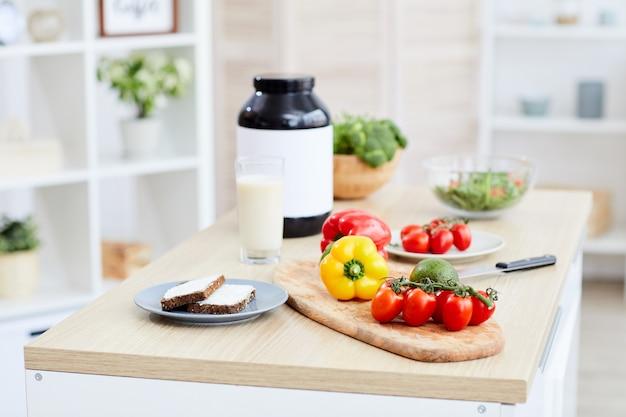 Nahaufnahme von frischem gemüse und flasche mit der richtigen ernährung auf dem tisch in der küche zu hause