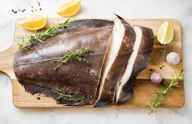 Nahaufnahme von frischem rohem heilbuttfisch auf holzbrett mit kräutern und zitrone. ansicht von oben. omega-3-fette sind gut für geistige klarheit. gehirnnahrung
