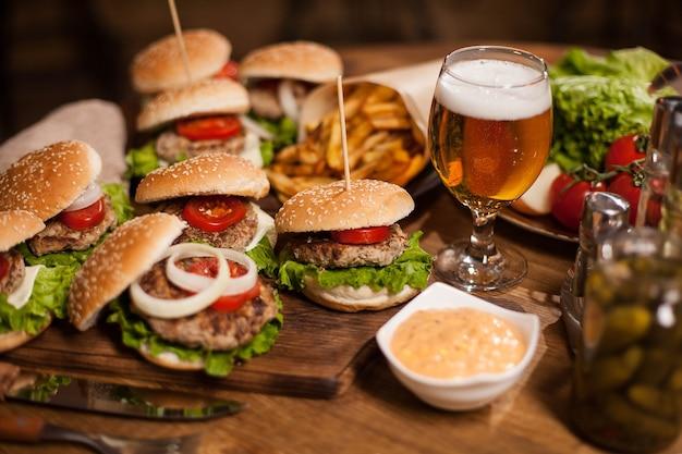 Nahaufnahme von frischen burgern mit einem glas bier auf vintage holztisch. leckeres fleisch. leckere gurken. frisches brot. tolles bier.