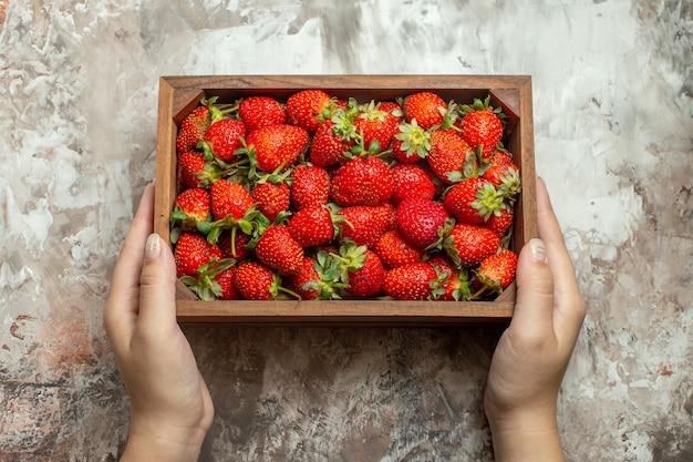Nahaufnahme von frischen erdbeeren in einer kleinen braunen holzkiste