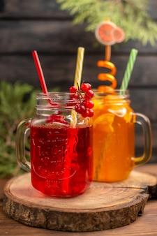 Nahaufnahme von frischen fruchtsäften in gläsern, die mit röhren auf einem holzbrett serviert werden