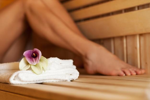 Nahaufnahme von frischen handtüchern und blumen in der sauna