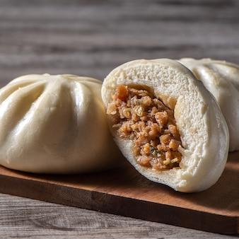 Nahaufnahme von frischen köstlichen baozi, chinesisches gedämpftes fleischbrötchen ist bereit, auf servierteller und dampfer zu essen, nahaufnahme, kopieren raumproduktdesignkonzept.