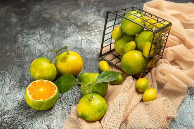 Nahaufnahme von frischen kumquats und zitronen in einem gefallenen schwarzen korb auf handtuch und vier zitronen auf grauem hintergrund