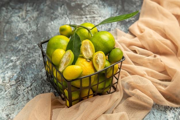 Nahaufnahme von frischen kumquats und zitronen in einem schwarzen korb auf handtuch auf grauem hintergrund
