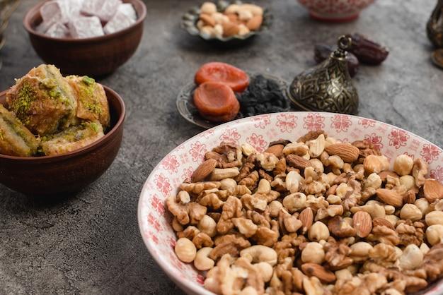 Nahaufnahme von frischen mischnüssen mit baklava auf hintergrund