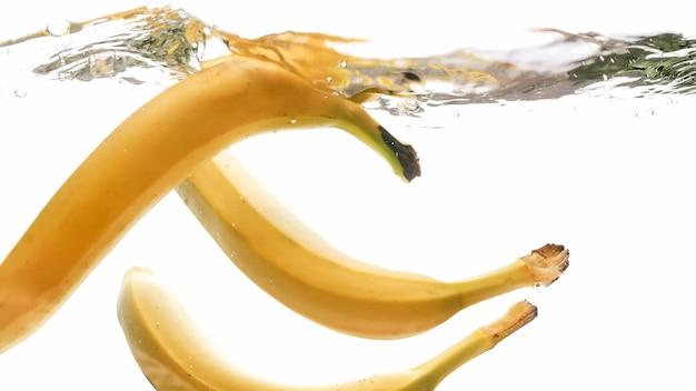 Nahaufnahme von frischen reifen bananen, die in wasser vor weißem, isoliertem hintergrund fallen und spritzen