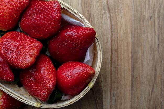 Nahaufnahme von frischen und natürlichen erdbeeren (große erdbeeren) im weidenkorb. mit kopierplatz. draufsicht.