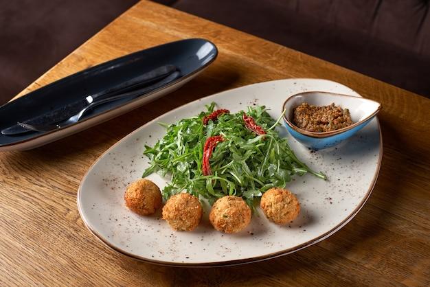 Nahaufnahme von frischer falafel mit sonnengetrockneter tomaten-pesto-sauce.