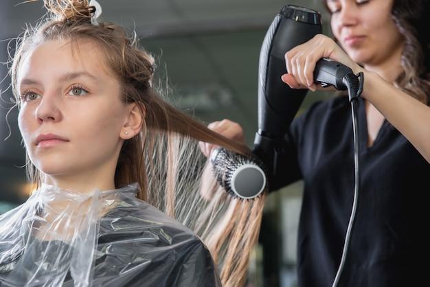 Nahaufnahme von friseurhänden, die langes blondes haar mit föhn und rundbürste trocknen