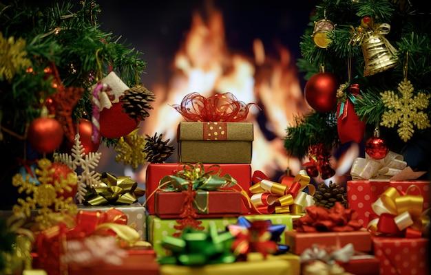 Nahaufnahme von frohen weihnachtsabend verpackten geschenkboxen mit rot-grünem und goldenem band mit dekoration