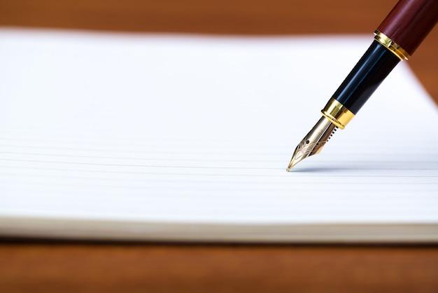 Nahaufnahme von füllfederhalter oder kugelschreiber mit notebook