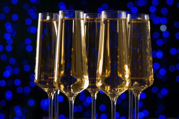 Nahaufnahme von fünf weingläsern auf blauen bokehlichtern. ein beliebtes alkoholisches getränk.