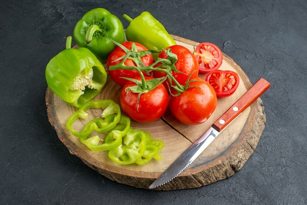 Nahaufnahme von ganzen geschnittenen gehackten grünen paprika und frischem tomatenmesser auf holzbrett auf schwarzer oberfläche