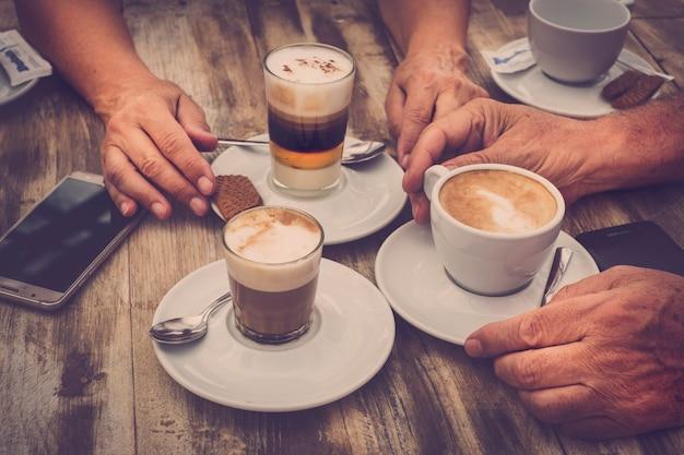 Nahaufnahme von gealterten kaukasischen händen mit kaffee-cappuccino an der bar zum frühstück - holztisch und romantische vintage-farbtöne - handy mit den leuten - liebes- und paarkonzept